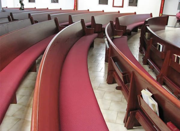 curved pew with maroon colored cushion