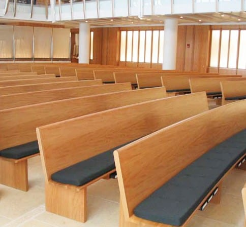 close up of curved pews with padded seats