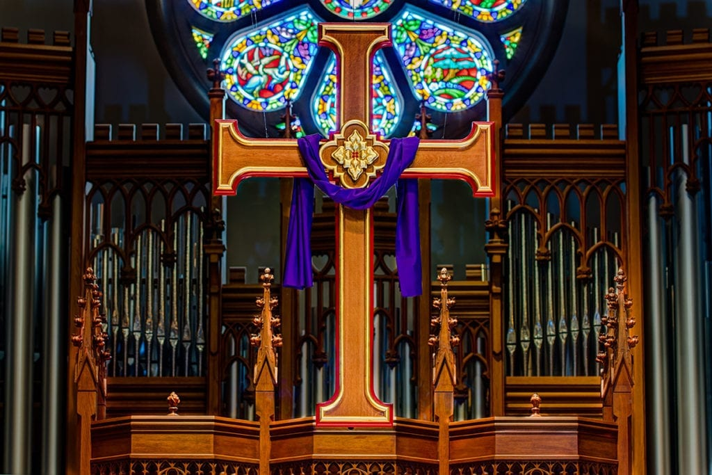 cross with stained glass in background