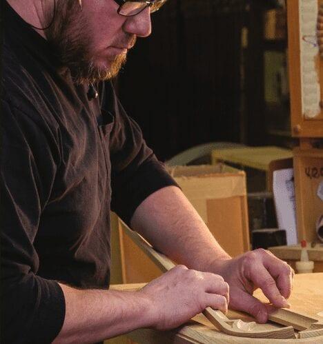 employee working on sanding wooden pieces