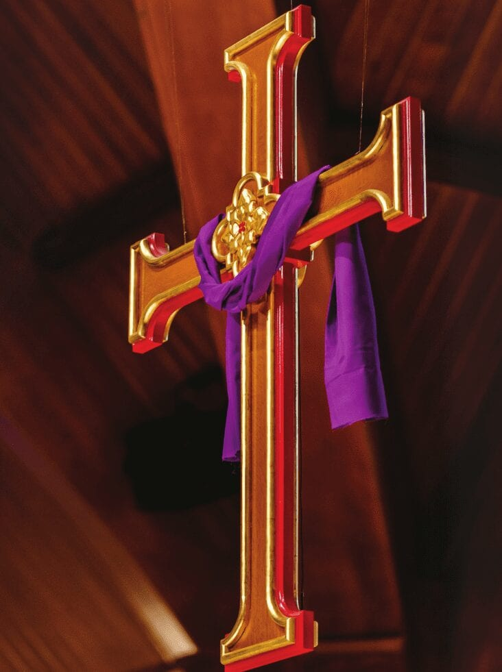 gold inlay on cross with purple drape